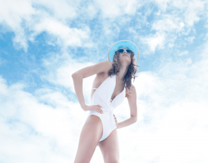 Women in white swim suit posing with beautiful clouds behind her.